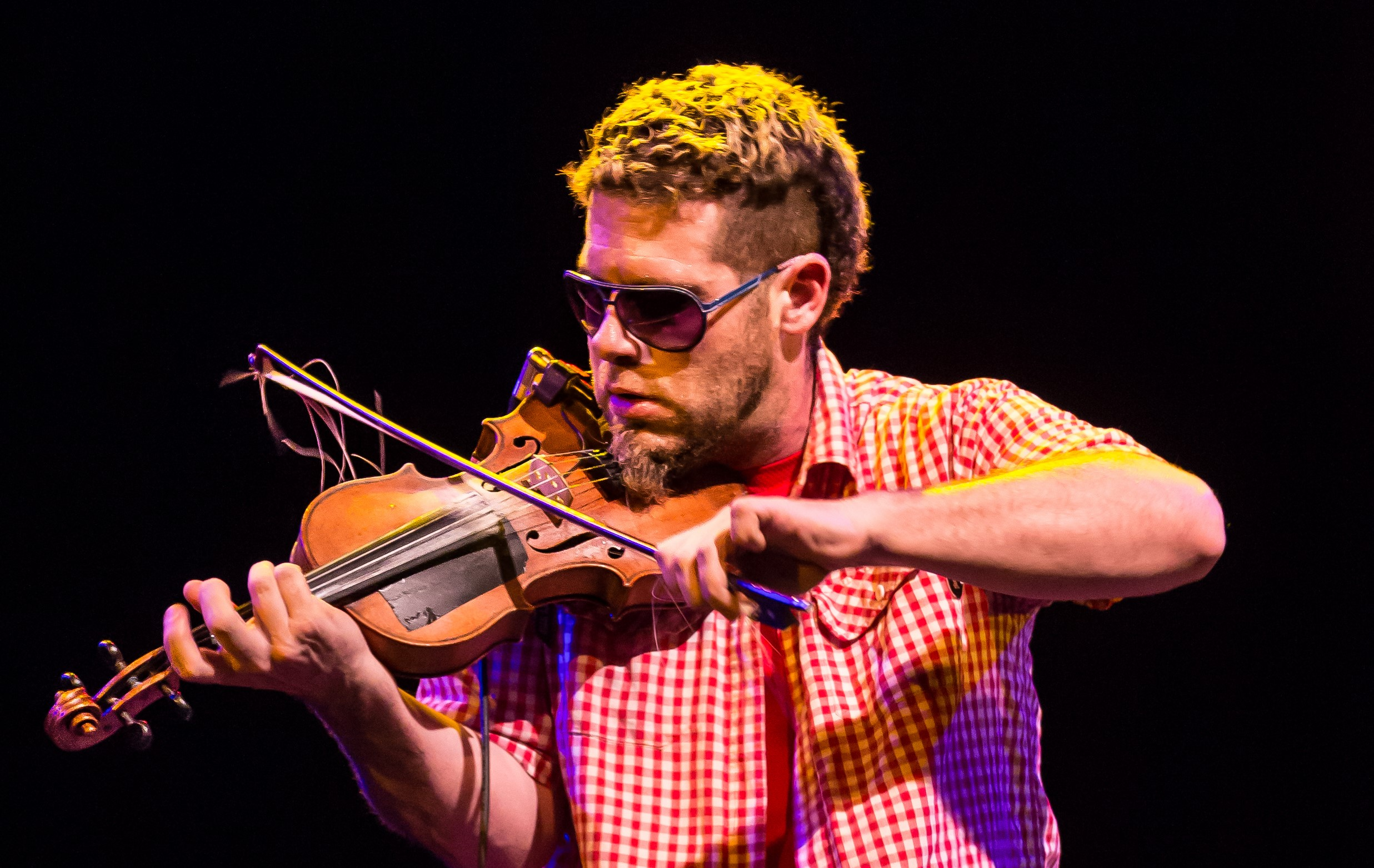 A close up of Ashley MacIsaac playing the fiddle.