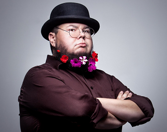 Shane Koyczan dressed in a top hat, with flowers in his beard!